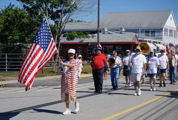 Joann Leishing leads the parade waving her flag while also wearing a flag ... and her omnipresent smile.