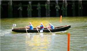 "In ""three-hand"" currach as member of Kildysart Team of Ireland, Plumleigh rows center seat in Ocean to City Festival in early June in Cork, Ireland."