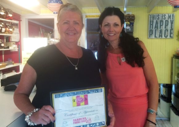 Barbara Crowley, owner of The Chocolate Shell (left) stands with OL-PGN Children's Librarian Julie Bartley after Bartley has presented Crowley with a certificate in appreciation of her support of the Summer Reading Program.