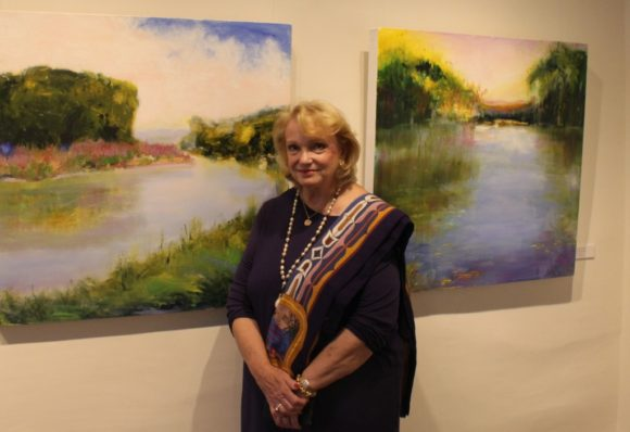 Jan Dilenschneider stands in front of a dyptych - a pair - of her paintings in the Sill House Gallery.