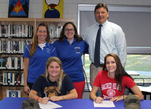 Sydney Cowell (seated left) and Anna Mesham (seated right) sign National Letters of Intent proudly watched by (from left to right) Lyme-Old Lyme High School (LOLHS) Athletic Director Hildie Heck, LOLHS Girls' Lacrosse Coach Emily Maciano and LOLHS Principal Jim Wygonik. standing,