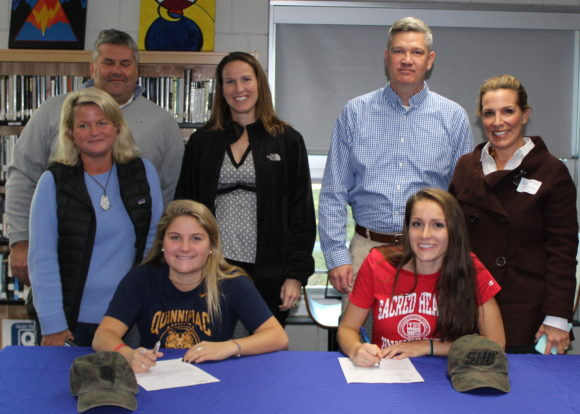 Proud parents Peter and Chrissy Cowell of Old Lyme watch as their daughter Sydney (left, seated) signs her National Letter of Intent to play lacrosse at Quinnipiac University after graduation from Lyme-Old Lyme High School. Similarly, John and Nancy Mesham of Old Lyme watch as daughter Anna (seated right) signs to play at Sacred Heart University. The girls Nor'easter club team coach (wearing black jacket) stands in the center.